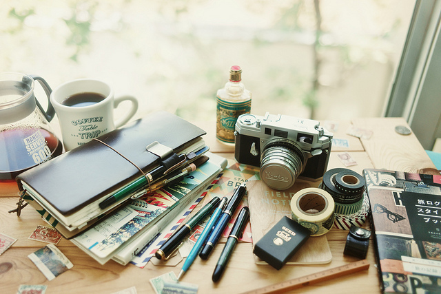 Coffee, a notebook and camera on a table