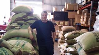 Man standing next to sacks of coffee