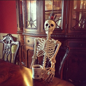 Skeleton holding a cup of coffee